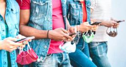giovani che scrivono e guardano lo smartphone ai tempi del Covid-19